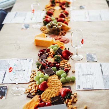 Grazing table with wine glasses, cheese, chocolates and other tasting snacks