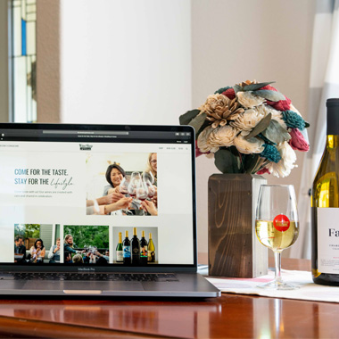 A laptop, glass of wine, a wine bottle and bouquet of flowers on a wooden table